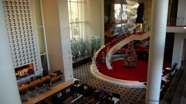 CU Grand high ceiling hotel lobby and curving staircase that wraps around corkscew shaped hanging LED chandelier / Hollywood, California, USA