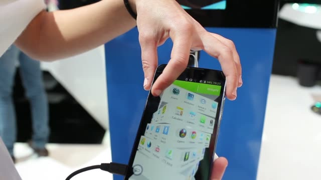 vídeos de stock e filmes b-roll de zte grand memo smartphone on display at the mobile world congress in barcelona the hand of an employee demonstrates a zte corp smartphone at the... - exposição
