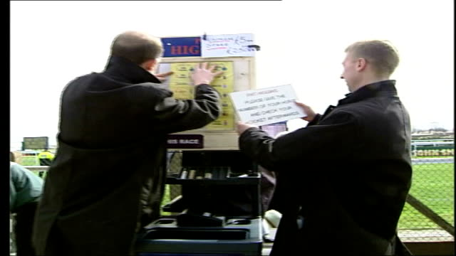 Grand National 2006 Nina and Paul Carberry interview SOT Bookies putting up odds on boards People including glamorously dressed women along at race...
