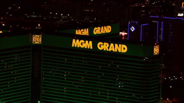 vídeos de stock, filmes e b-roll de grand neon signs on the mgm grand las vegas hotel & casino building, to xws flying mgm grand building on las vegas boulevard, aka the strip. - estação turística