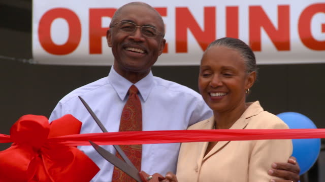 ms grand opening sign with balloons/ td man with arm around wife as she cuts ribbon with giant scissors/ ms man and woman smiling and high fiving/ richmond, virginia - cutting stock videos & royalty-free footage