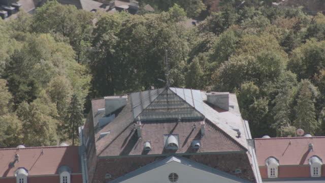 vídeos y material grabado en eventos de stock de aerial grand, red-roofed, multi-story, white estate, parking area, and surrounding gardens atop wooded, green hill - formato buzón