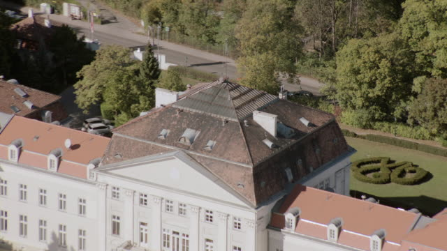 aerial grand, red-roofed, multi-story, white estate, parking area, and surrounding gardens atop wooded, green hill - stockwerk stock-videos und b-roll-filmmaterial