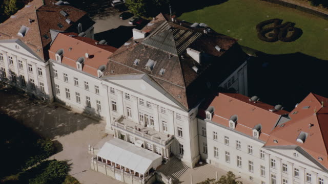 stockvideo's en b-roll-footage met aerial grand, red-roofed, multi-story, white estate with patio area and surrounding gardens atop wooded, green hill - breedbeeldformaat