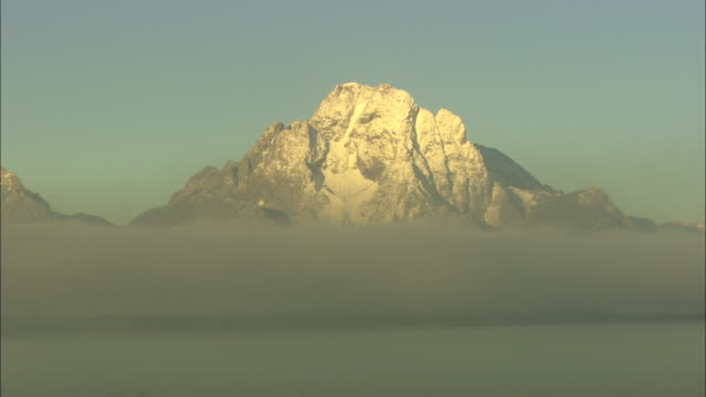 grand teton peak rises over clouds. - grand teton stock videos & royalty-free footage