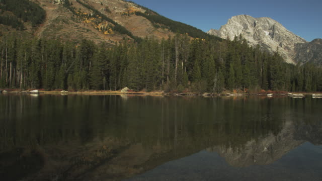grand teton reflects on the surface of string lake. - grand teton stock videos & royalty-free footage