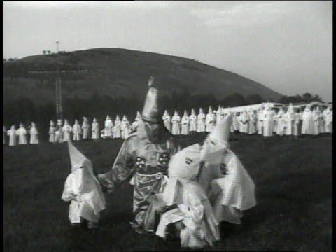 vídeos de stock, filmes e b-roll de grand wizard talking to children in little kkk robes and hoods while other klansmen watch / georgia united states - ku klux klan
