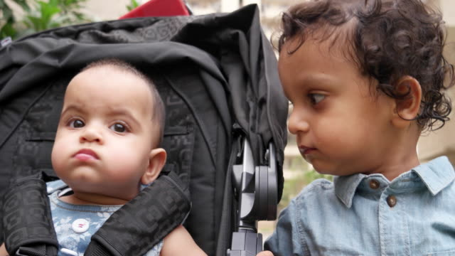 grandad with a beautiful grand-daughter seated in a stroller and identical twin grand-sons in a public playground - identical twin stock videos & royalty-free footage