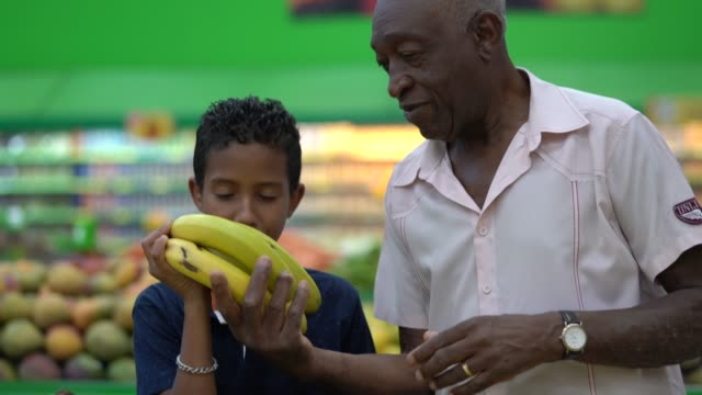 grandchild and grandfather buying on supermarket - banana stock videos & royalty-free footage