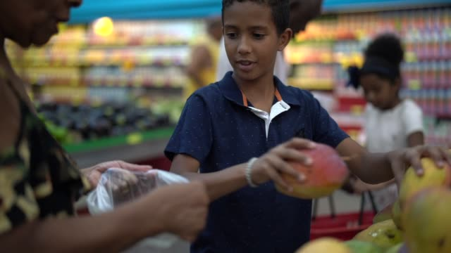 vídeos de stock, filmes e b-roll de neto e avó comprando no supermercado - rotina