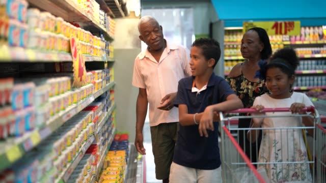 Grandchild and Grandparents buying on supermarket