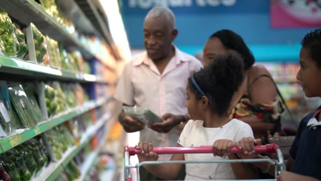grandchild and grandparents buying on supermarket - retirement stock videos & royalty-free footage