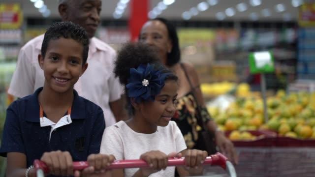 enkel und großeltern kaufen im supermarkt - großeltern stock-videos und b-roll-filmmaterial