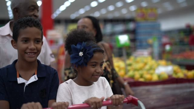vídeos de stock, filmes e b-roll de neto e os avós que compra no supermercado - rotina
