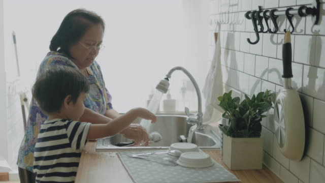 grandchild do dishes with grandmother in kitchen. - crockery stock videos & royalty-free footage