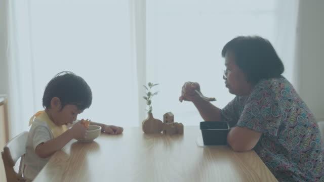 enkelkind essen udon mit großmutter auf dem tisch zu hause. - großeltern stock-videos und b-roll-filmmaterial