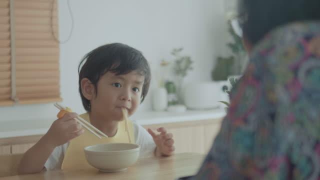 孫が家のテーブルの上でおばあちゃんとうどんを食べている。 - 大家族点の映像素材/bロール