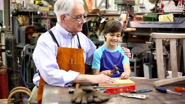 Grandchild in workshop with grandfather reparing antique furniture.