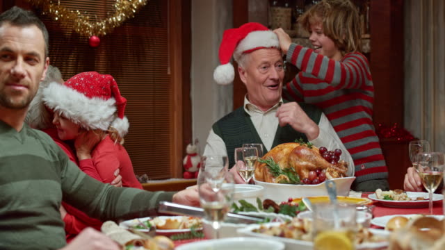 stockvideo's en b-roll-footage met grandchildren having fun with grandparents at the christmas table - avondmaaltijd