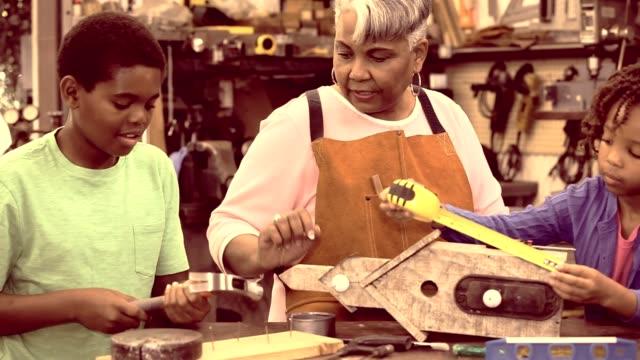 Grandchildren in workshop with active senior grandmother building birdhouses.