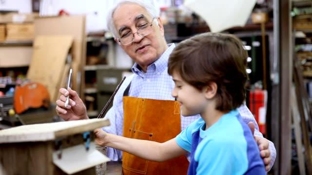 Grandchildren in workshop with grandfather building birdhouses.