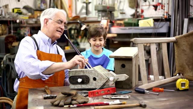 Grandchildren in workshop with grandfather repairing a birdhouse.