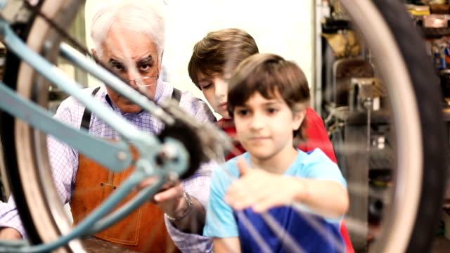 Enkelkinder im Workshop mit Großvater Fahrrad reparieren.