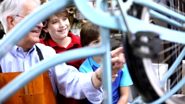 grandchildren in workshop with grandfather repairing bicycle. - grandson stock videos and b-roll footage