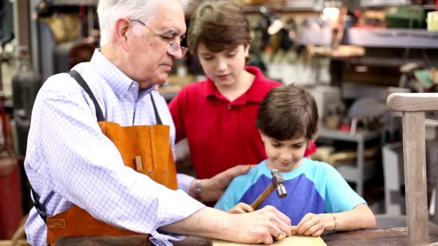 vidéos et rushes de petits-enfants en atelier avec grand-père réparer des meubles anciens. - septuagénaire