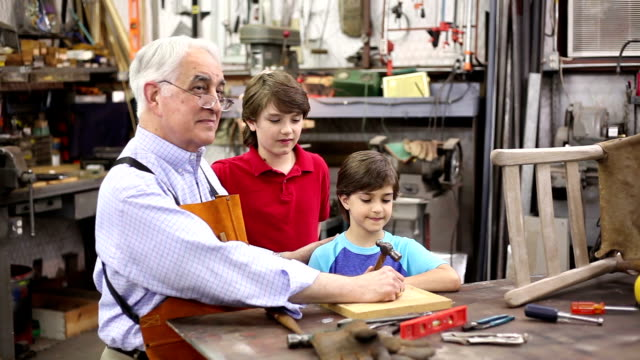 grandchildren in workshop with grandfather reparing antique furniture. - grandson stock videos and b-roll footage