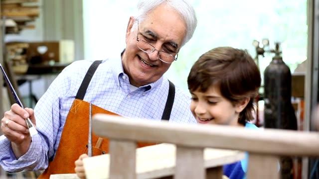 vídeos de stock, filmes e b-roll de netos na oficina com o avô reparing mobiliário antigo. - artesão