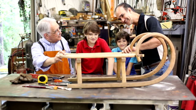 Grandchildren in workshop with grandfather reparing antique sled.