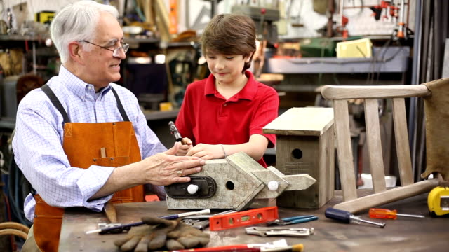 Grandchildren in workshop with grandfather work on a birdhouse.