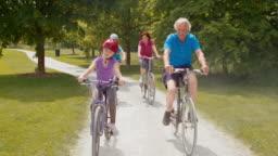 SLO MO Grandchildren riding bikes through park with grandparents