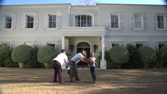 LA LS grandchildren running out to senior African couple outside house/ Cape Town/ South Africa