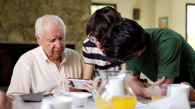 enkel lehren großvater, wie man ein smartphone verwendet - teenager alter stock-videos und b-roll-filmmaterial
