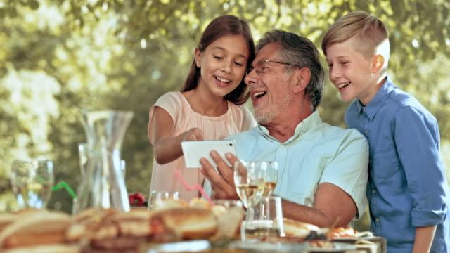 SLO MO opa zijn kleinkinderen foto's tonen op een smartphone