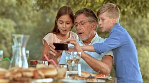 vídeos y material grabado en eventos de stock de slo mo abuelo tomando un selfie con sus nietos - nieto
