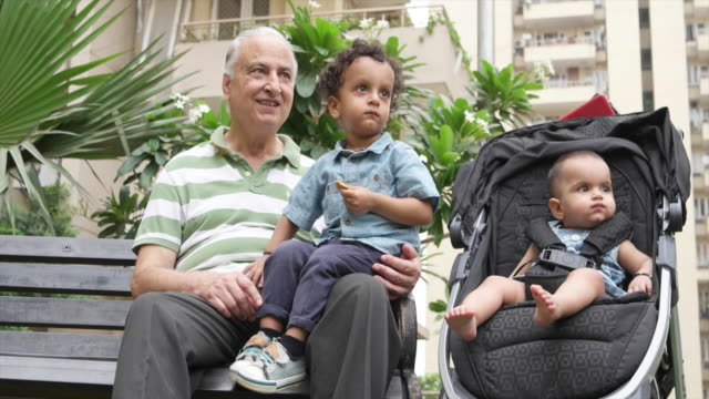 Grand-dad with his grand-son and grand-daughter in a playground in a multi storied residential complex