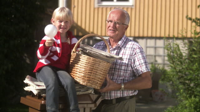 Granddaughter and grandfather by a dustbin, Sweden.