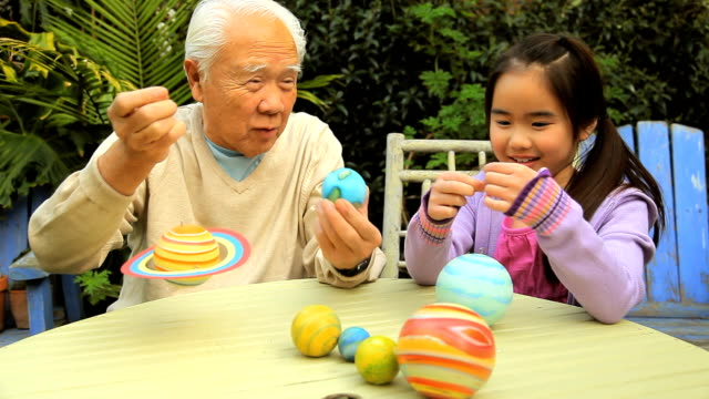 ms zi granddaughter (8-9) and grandfather dangling colorful planets at table / los angeles, california, usa - アクティブシニア点の映像素材/bロール