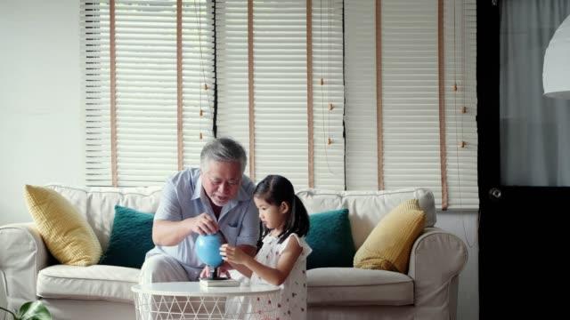 地球を見て、リビングルーム、教育の概念で地理を教える孫娘と祖父。子供の生活の日タイの家族。 - 余暇点の映像素材/bロール