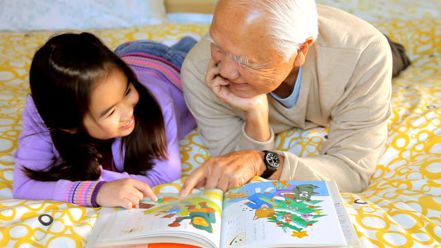 ms granddaughter (8-9) and grandfather looking at picture book / los angeles, california, usa - granddaughter stock videos & royalty-free footage