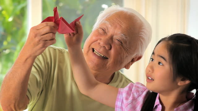 ms zo granddaughter (8-9) and grandfather playing with paper crane / los angeles, california, usa - 祖父点の映像素材/bロール
