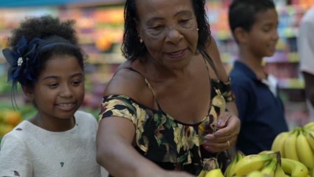 vídeos de stock, filmes e b-roll de neta e avó comprando no supermercado - rotina