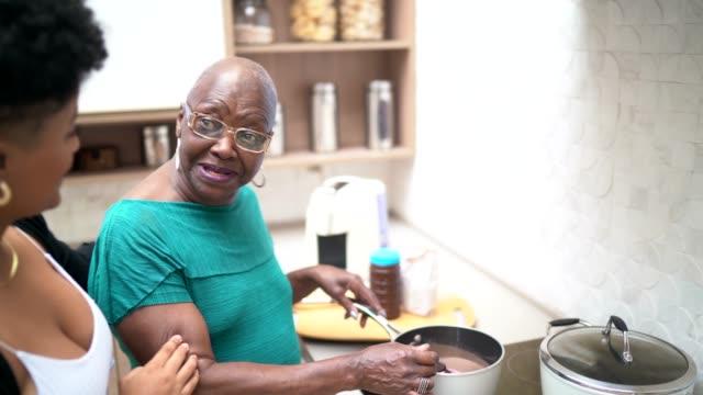 vídeos de stock, filmes e b-roll de neta e avó que cozinham junto - miscigenado