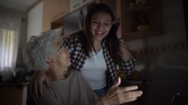 vídeos y material grabado en eventos de stock de nieta y abuela haciendo un videochat juntos en casa - rodar
