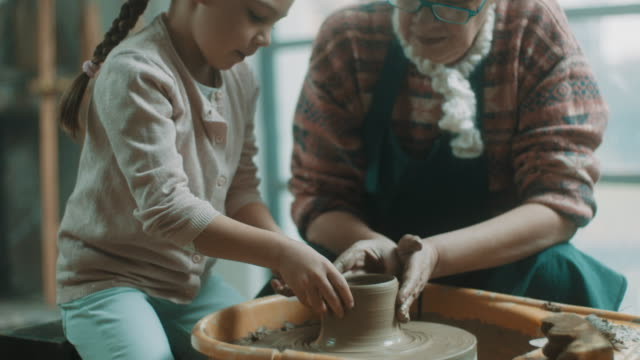 granddaughter and grandmother doing pottery together - potter stock videos & royalty-free footage