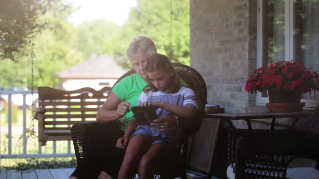 granddaughter and grandmother playing game on digital tablet