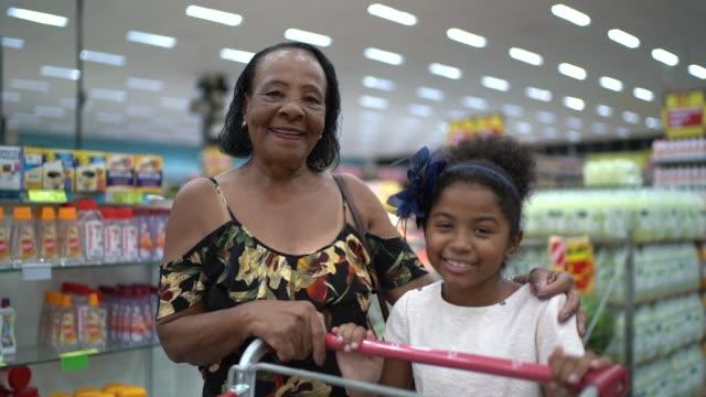 vídeos de stock, filmes e b-roll de retrato de neta e avó no supermercado - carrinho meio de transporte